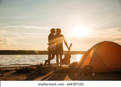 Back view of beautiful young couple with guitar standing and hugging on the sunset