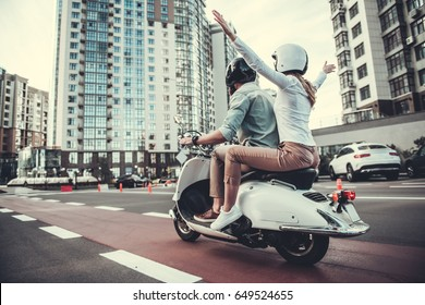 Back view of beautiful young couple in helmets riding a scooter
