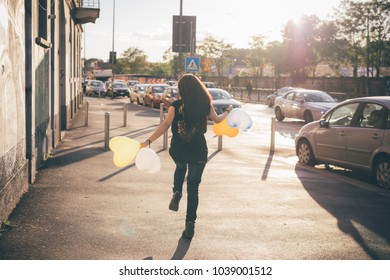 Back view of beautiful young woman outdoor in back light playing with balloon - happiness, having fun, childhood concept