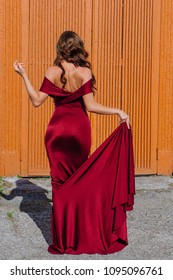 Back view of a beautiful young woman in a long red evening gown with a train standing next to the old door