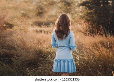 Back view of a beautiful young woman or girl on very green meadow watching the sunset enjoying nature summer evening outdoors. Sunshine.