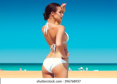 back view of beautiful young woman in white bikini with the blue sky and ocean in the background