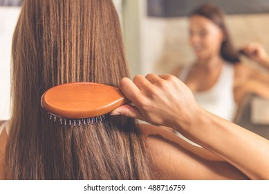 Back view of beautiful young woman in white undershirt combing her hair and smiling while looking into the mirror in bathroom