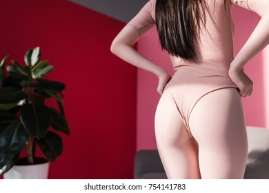 back view of beautiful young woman in bodysuit posing in studio