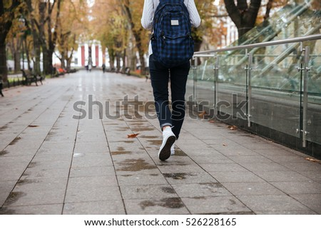 Back view of beautiful young woman with backpack walking in park