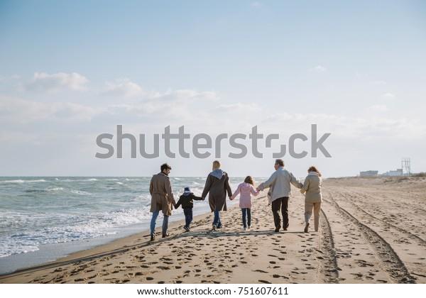 back view of big multigenerational family walking together on seashore