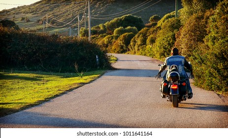 Back view of a biker on a classic motorcycle on a country road