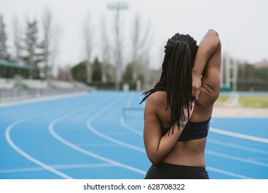 Back view of black female in sportswear stretching shoulders on sports ground.