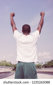 Back view of black man celebrating sport success. Young Afro American in sports wear raising hands and enjoying park and city view. Open air workout and sport achievement concept