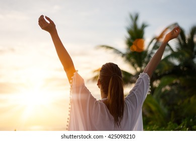 Back view of blissful woman at tropical beach enjoying relax, freedom and vacation.  Female raising arms towards the sun on beautiful sunrise. Summer happiness and leisure.