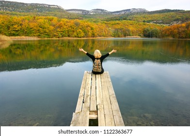 Back view of blond hiker woman with backpack sitting on old wooden pier over calm lake with autumnal hills in background.