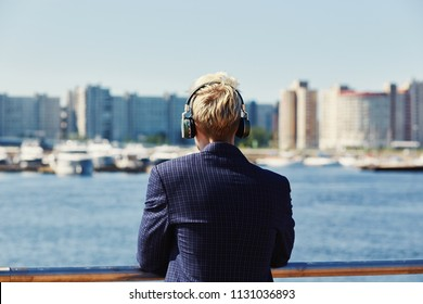 Back view of blond male in dark checkered jacket leaning on metal railing of embankment and looking at water, boats and buildings on blurred background