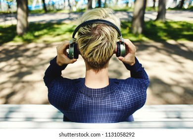 Back view of blond man in dark clothes sitting on white sunlit park bench putting grey headphones on head on blurred background