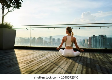 Back view of blonde hair woman in white tracksuit sitting in yoga pose while meditating in warm summer evening on rooftop floor with scenery city view. Female with slim body enjoying yoga training