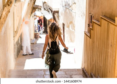 back view of a blonde tourist woman walking through the city on her vacation trip in the streets of morocco