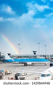 Back view of blue aircraft in an airport. Beautiful rainbow and blue sky in background.