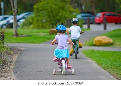 Back view of boy and girl riding bicycles in a park