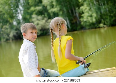 Back view of boy and girl sitting on wooden pier with rod