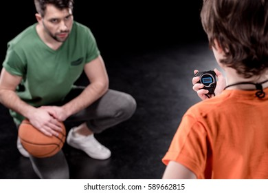 back view of boy with stopwatch controlling time while man training isolated on black