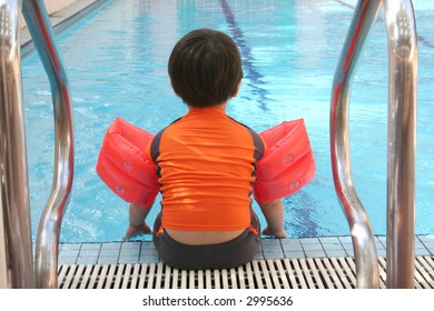 Back view of boy with swimsuit sitting at the swimming pool