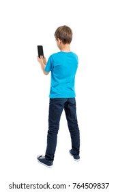 Back view of boy in t-shirt and jeans talking on mobile phone isolated on white background