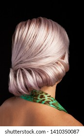 Back view of bridal coiffure on a young woman with silver hair. Bright color hair. Isolated on studio background.