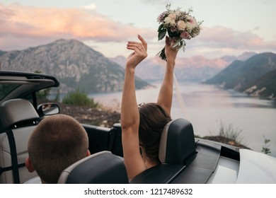 Back view of bride and groom in cabriolet car with hands raised up against the sea