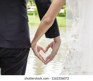 Back view of bride in white dress and groom in suit holding hands heart shape earnestly wedding theme