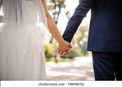 Back view of bride in white dress and groom in suit holding each others hands outdoors