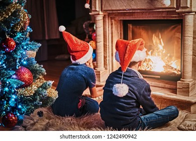 Back view, brother and sister wearing Santa's hats warming next to a fireplace in a living room decorated for Christmas.