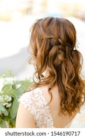 Back view of brown curls for bride keeping flowers. Concept of wedding photo session and stylish hair do.