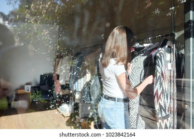 Back view of brunette customer looking at knitted sweater in shop. View through the window.