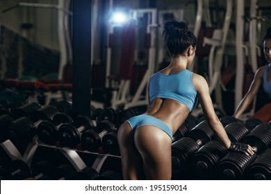 Back view of brunette sexy fitness girl in blue sport wear with perfect body in the gym posing