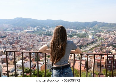 Back view of brunette watching summer cityscape.Barcelona,Catalonia.