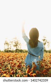 Back view of brunette young woman walking in red poppy flower field on sunny summer day. Romantic girl waving her hand to the sun.