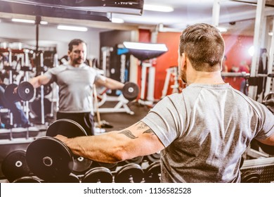 Back view of brutal sportsman raising dumbbells laterally training in front of mirror in gym.