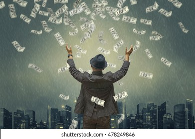 Back view of business man hug money with green tones dramatic rain & city background. Concept for success business. Motion blur money.
