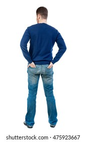 back view of Business man looks. bearded man in blue pullover standing with his hands in the back pockets of his pants.
