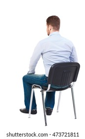 back view of business man sitting on chair. Bearded businessman in white shirt sits on a chair and looking forward.