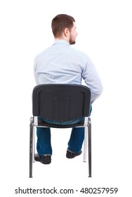 back view of business man sitting on chair. Bearded businessman in white shirt sits on a chair and looks sideways.