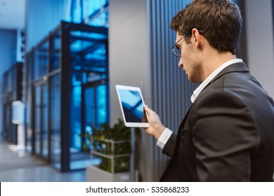 Back view of Business man in suit and glasses with laptop computer in office