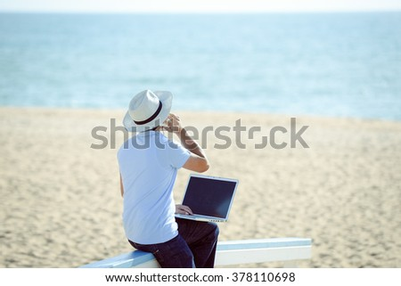 Back view of business man working with computer and talking on smartphone. Sandy beach, blue sea and sky background