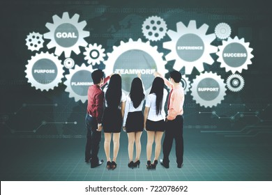 Back view of business people is touching a cogwheel on the virtual screen while standing together