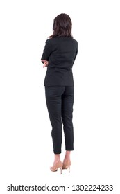 Back view of business woman in black suit with crossed arms watching interested. Full body isolated on white background.