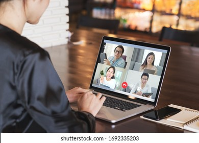 Back view of business woman talking about sale report in video conference. Asian team using laptop and tablet online meeting in video call.Working from home, Working remotely and Social isolation.