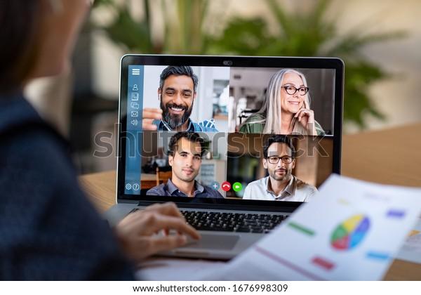 ビジネスマンが同僚とビデオ会議で計画について話す様子。ビデオ通話でノートパソコンをオンラインミーティングに使用する複数民族のビジネスチーム。自宅でスマートに働く人のグループ