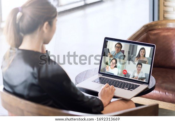 Back view of business woman talking about sale report in video conference. Asian team using laptop and tablet online meeting in video call.Working from home, Working remotely and Self isolation.