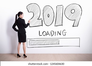 Back view of business woman writing 2019 new year on white wall background