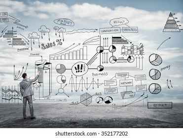 Back view of businessman drawing business plan sketches