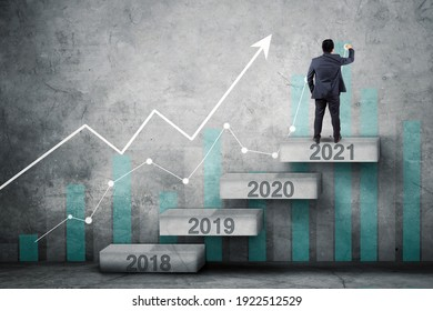 Back view of businessman drawing upward arrow and growth chart while standing on the stair with numbers 2021